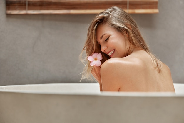 Blonde woman relaxing in bathtub with petals