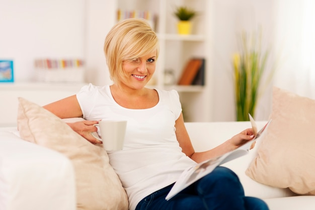Blonde woman relaxing at home with coffe and newspaper