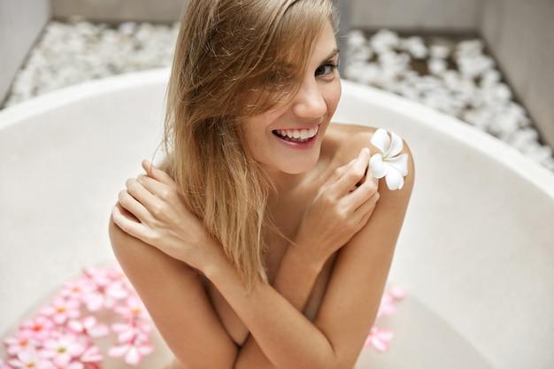 Блондинка расслабиться в ванне с лепестками