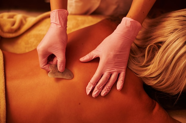 Blonde woman relaxing on a massage table during chinese traditional massage - gua sha