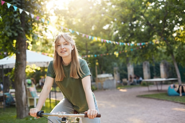 Blonde woman riding a bike. portrait of young nordic woman riding a bycicle in a city park smilinglifestyle concept.
