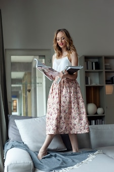 Blonde woman in romantic outfit, standing on the couch with bare feet holding magazines in hands