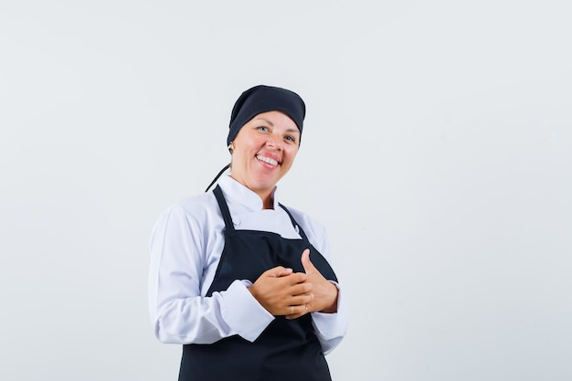 Blonde woman rubbing hands in black cook uniform and looking pretty , front view.