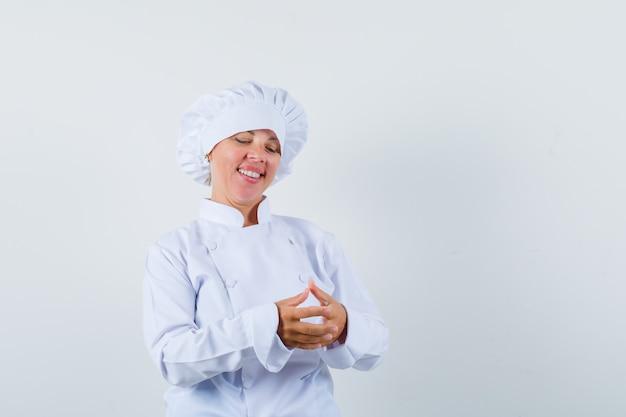 Donna bionda che strofina le mani in uniforme bianca del cuoco e che sembra carina