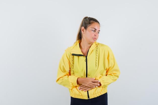 Donna bionda strofinando le mani in bomber giallo e pantaloni neri e guardando pensieroso