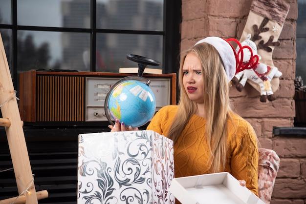 Donna bionda in cappello della santa che esamina globo.