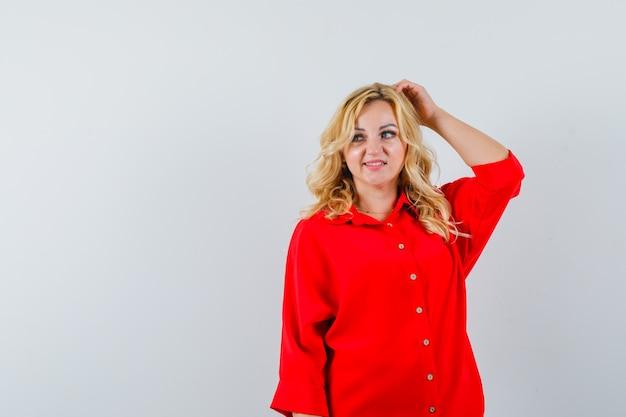 Donna bionda che graffia la testa, distoglie lo sguardo in camicetta rossa e sembra carina, vista frontale.