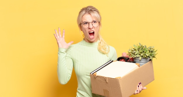 Blonde woman screaming with hands up in the air, feeling furious, frustrated, stressed and upset