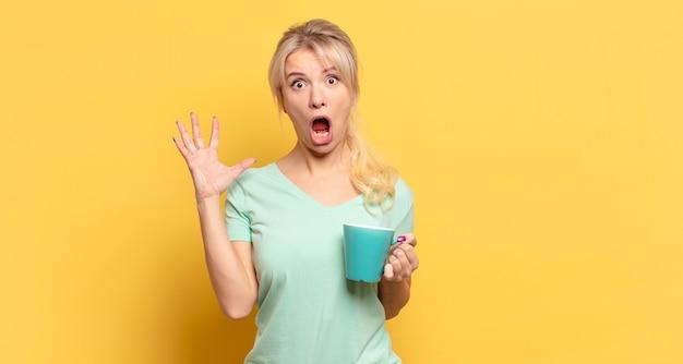 Блондинка кричит с поднятыми руками, чувствуя ярость, разочарование, стресс и расстройство