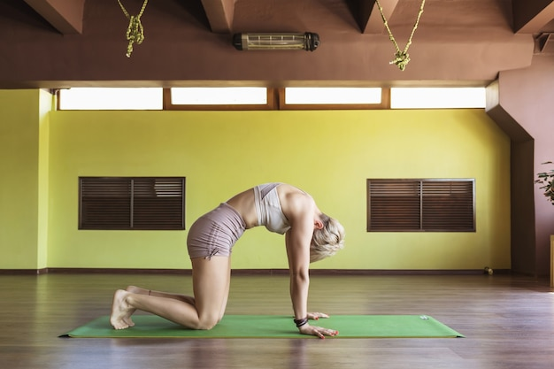 A blonde woman in shorts and a short tshirt practicing yoga