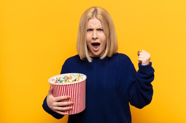 Блондинка агрессивно кричит с гневным выражением лица или со сжатыми кулаками празднует успех