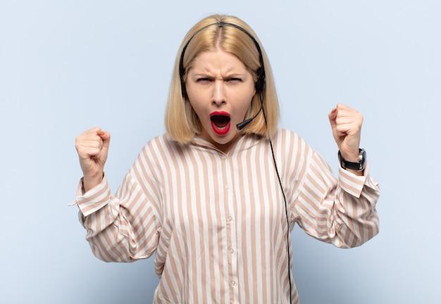 화난 표정으로 또는 주먹으로 공격적으로 외치는 금발의 여인이 성공을 축하합니다.
