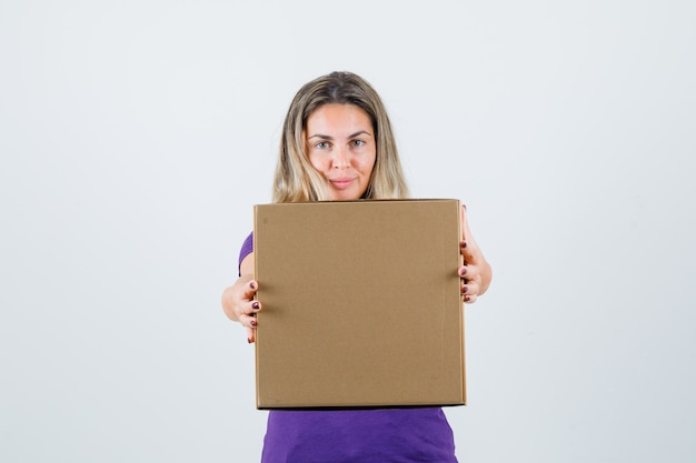 Blonde woman showing cardboard box in violet t-shirt front view.