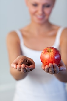 チョコレートとリンゴをチョコレートとリンゴに見せるブロンドの女性