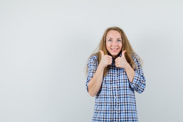 금발 여자 셔츠에 두 엄지 손가락을 보여주는 행복을 찾고,