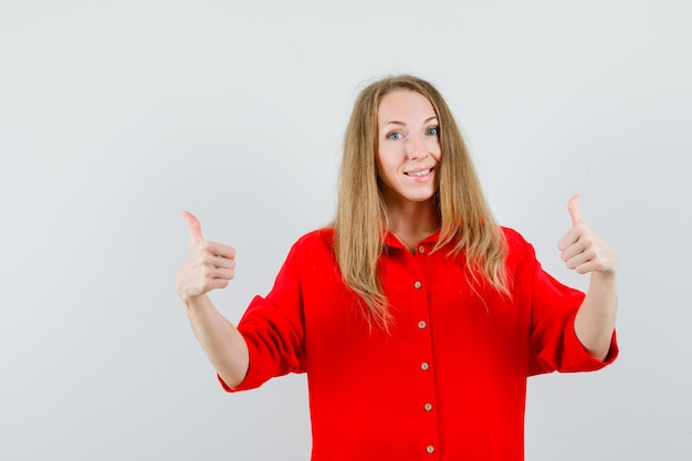 Blonde woman showing double thumbs up in red shirt and looking glad.