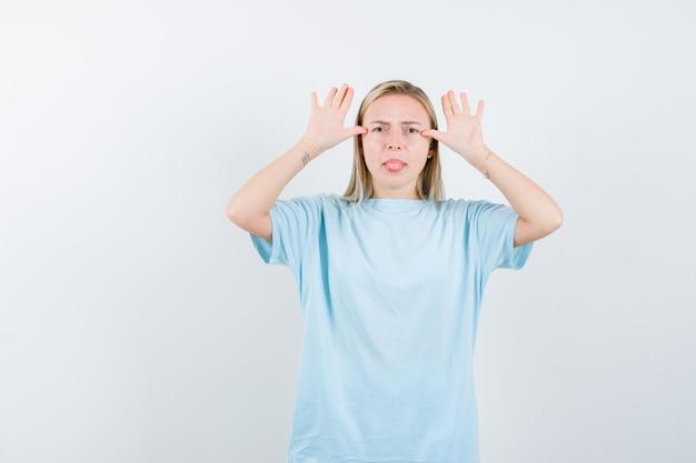 耳のジェスチャーを示し、青いtシャツで舌を突き出し、面白がって見える金髪の女性