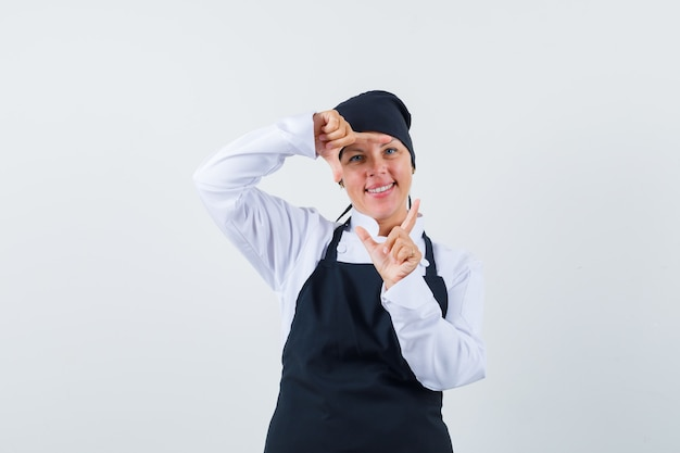 Blonde woman showing frame gesture with hands in black cook uniform and looking pretty , front view.