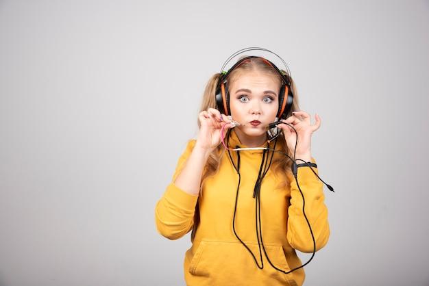 灰色の背景にヘッドフォンを示す金髪の女性。