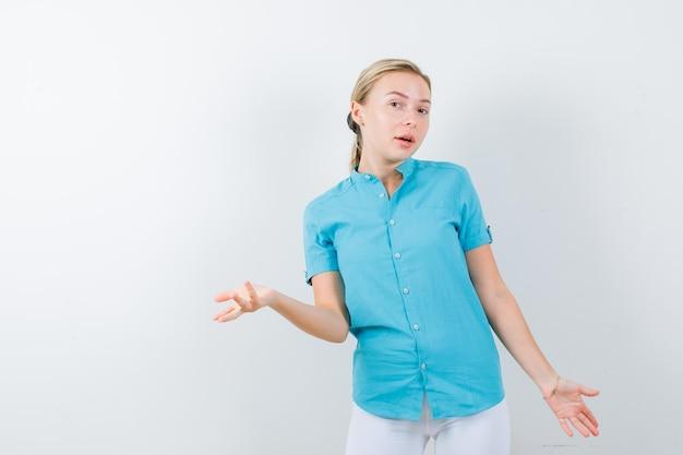 Donna bionda che mostra gesto impotente in camicetta blu e sembra confusa