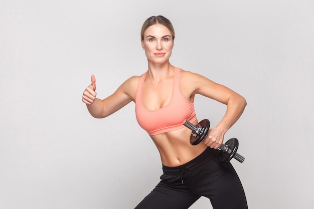 Blonde woman showing like sign and holding dumbbell. studio shot