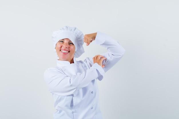 흰색 요리사 유니폼에 근육을 보여주는 금발의 여자와 예쁜 찾고.