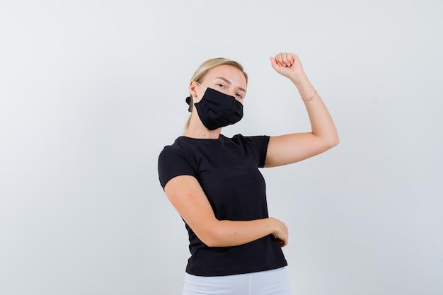 검은 티셔츠, 흰색 바지에 팔의 근육을 보여주는 금발의 여자