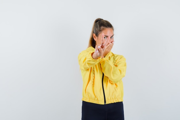 Blonde woman showing peace gesture in yellow bomber jacket and black pants and looking happy