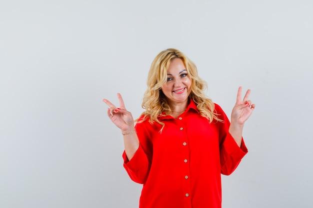 Donna bionda che mostra gesti di pace con entrambe le mani in camicetta rossa e che sembra felice, vista frontale.