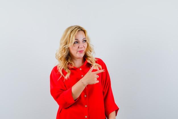Donna bionda che mostra il segno di pace in camicetta rossa e che sembra felice.