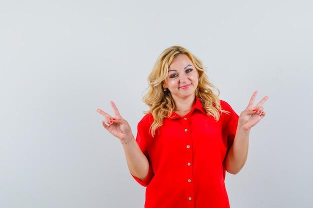 Donna bionda che mostra il segno di pace con entrambe le mani in camicetta rossa e che sembra felice.