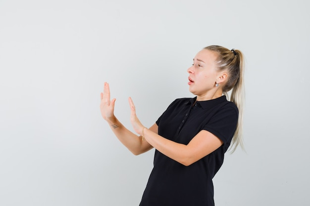 Donna bionda che mostra rifiuta o nega il gesto in maglietta nera e sembra spaventata