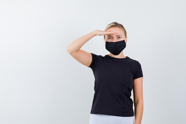Blonde woman showing salute gesture in black t-shirt