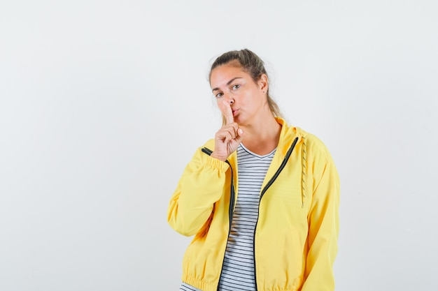 Блондинка демонстрирует жест тишины в желтом бомбере и полосатой рубашке и смотрит сосредоточенно