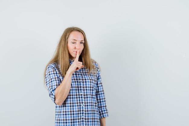 Блондинка показывает жест молчания, подмигивает в рубашке и выглядит уверенно.