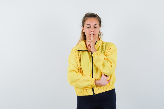 Blonde woman showing silence gesture in yellow bomber jacket and black pants and looking focused