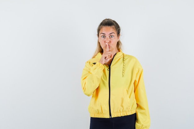 Blonde woman showing silence gesture in yellow bomber jacket and black pants and looking serious