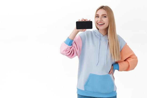 Блондинка показывает экран смартфона