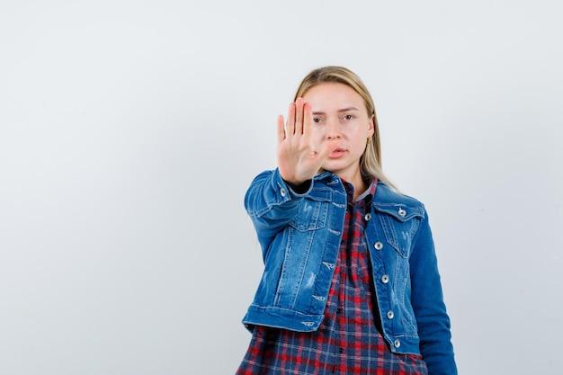 シャツ、ジャケット、毅然とした表情で停止ジェスチャーを示すブロンドの女性。