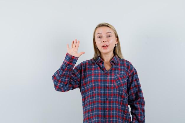 체크 셔츠에 정지 신호를 표시 하 고 낙관적, 전면보기를 찾고 금발 여자.