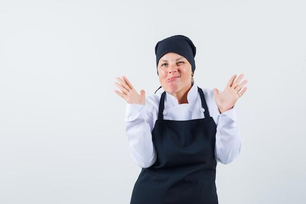 금발의여자가 양손으로 정지 신호를 보여주는 검은 요리사 유니폼에 찡그린 하 고 예쁜 찾고. 전면보기.
