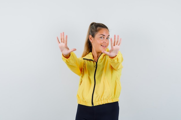 Blonde woman showing stop sign with both hands in yellow bomber jacket and black pants and looking pretty