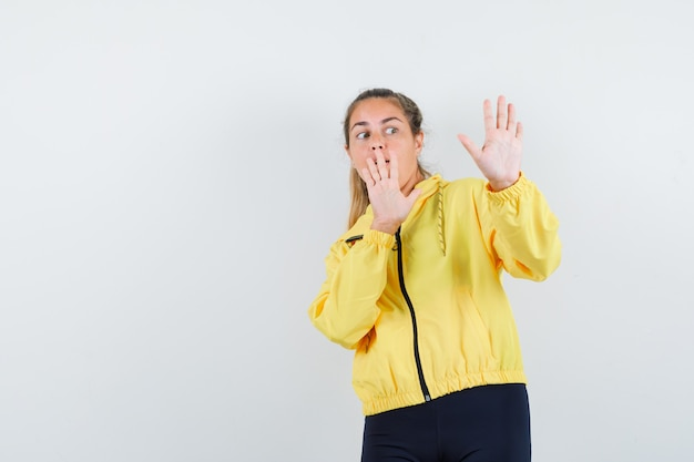 Blonde woman showing stop sign with both hands in yellow bomber jacket and black pants and looking scared
