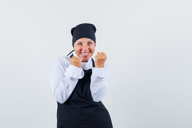 Blonde woman showing success gesture in black cook uniform and looking happy. front view.