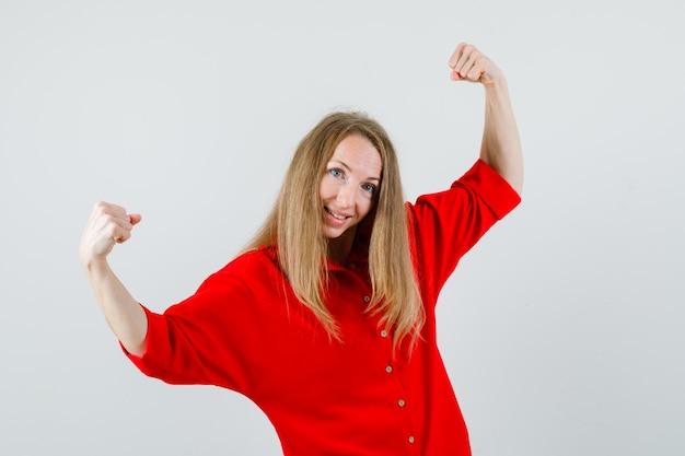 Donna bionda che mostra il gesto di successo in camicia rossa e che sembra allegra,