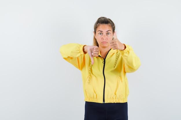 Блондинка показывает большой палец вверх и вниз в желтой куртке-бомбардировщике и черных штанах и выглядит красиво