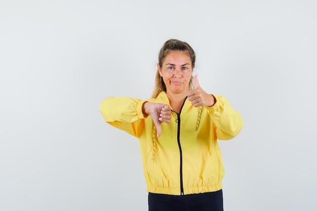 Donna bionda che mostra il pollice su e giù in bomber giallo e pantaloni neri e sembra carina