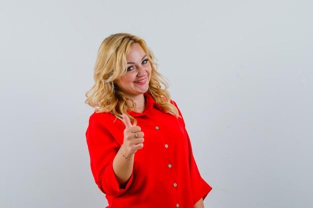 赤いブラウスで親指を表示し、幸せそうに見える金髪の女性。