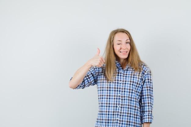 Блондинка показывает палец вверх, подмигивает в рубашке и выглядит уверенно