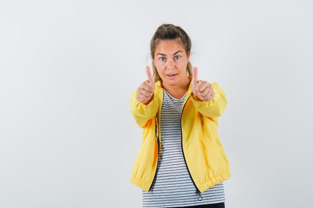 黄色のボンバージャケットとストライプのシャツで両手で親指を見せて、きれいに見える金髪の女性